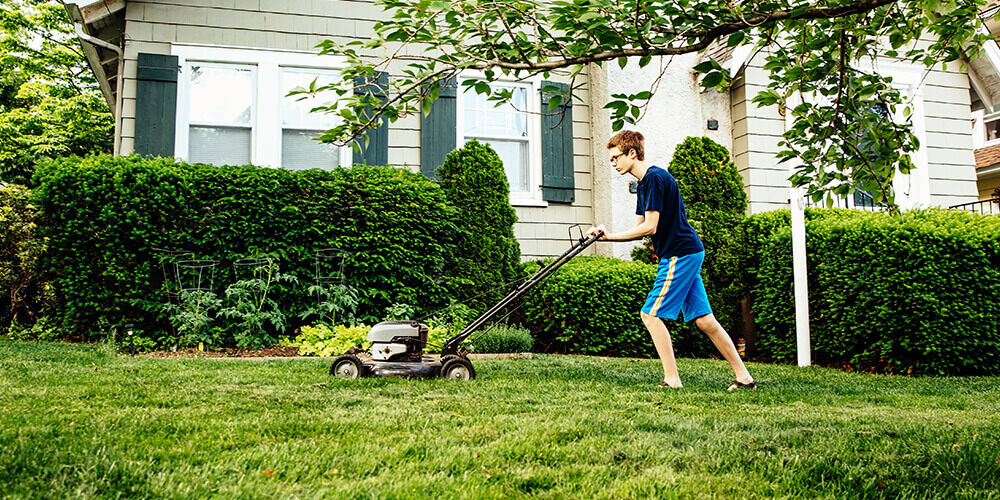 A tween boy in light blue shorts and a dark blue shirt and glasses, pushes a lawn mower to cut his front lawn.