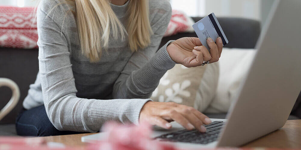 A woman in a gray sweater sits on her couch using her debit card to make holiday gift purchases from her laptop