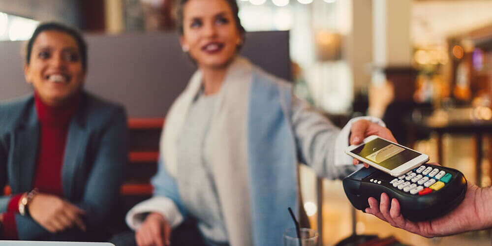 A woman in a light blue coat is sitting with her friend in a red shirt and gives her phone to pay for their lunch
