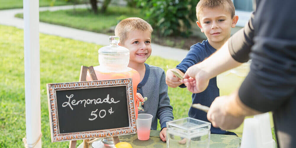 Two young boys receive money from a customer at the lemonade stand they have set up in their front yard.