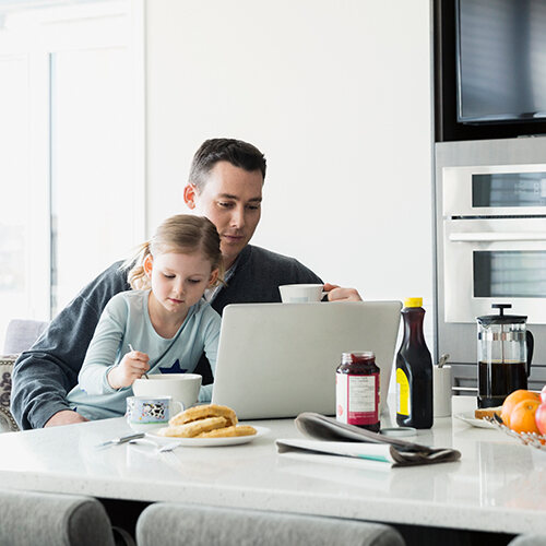Dad sips coffee looking at laptop while young daughter sits in lap in PJs stirring a spoon in a bowl at the kitchen table