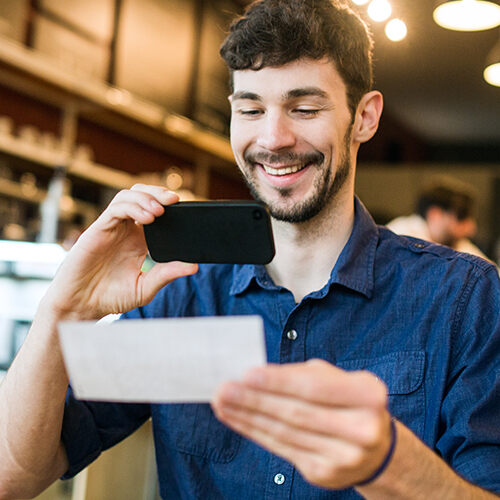 Bearded man smiles showing his friend how easy it is to make a mobile deposit to his bank from the comfort of a café