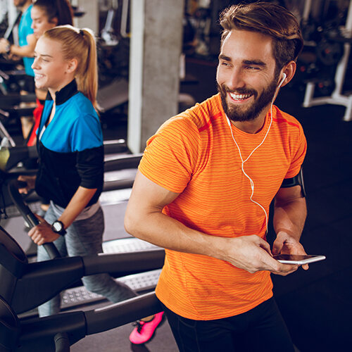 Fit man in orange shirt leaning against a treadmill in a gym with his phone in hand and earbuds laughing