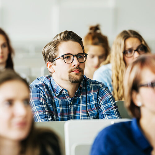 A male college student in glasses and blue plaid shirt looks forward listening to the professor's lecture.