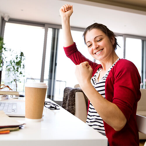 A young woman in a striped shirt and red sweater sits at a desk in her living room and raises her arms in celebration.