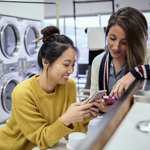 Two young women enjoying their mobile phones while at a laundromat