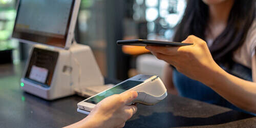 A woman at checkout holds her mobile phone over a card reader using digital wallet to make a contactless payment
