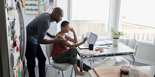 Woman seated at table checks laptop while man behind her leans over with mobile phone in hand