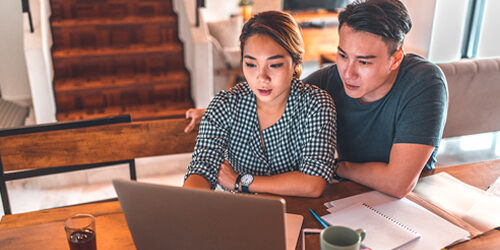 A woman in a plaid shirt sits with her husband in a gray tshirt at a table by the stairs and uses a laptop and paperwork to plan out their finances