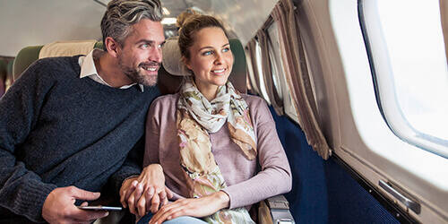 Smiling couple holding hands while seated and looking out an airplane window