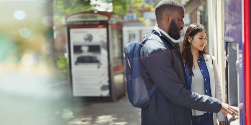 Man with beard and backpack stands with woman to use the ATM on the street