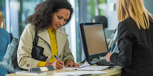 Woman in trench coat deposits check at her bank branch while bank teller checks online account information