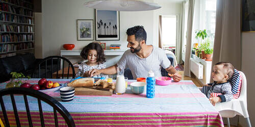 Father helping his daughter on her tablet seated at the dining room table with bread and milk