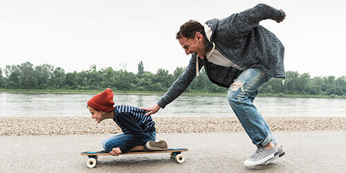 Happy father running and pushing his excited young son kneeling on a skateboard