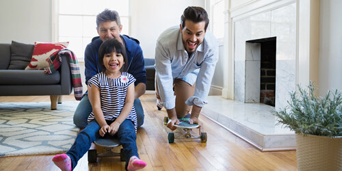 Two men in blue shirts and a young girl in a striped shirt smile and laugh as they ride on skateboards past a fireplace in a living room.