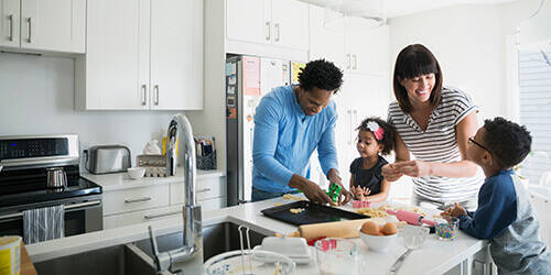 Brightly-lit kitchen with father, mother, daughter and son cutting out cookie dough