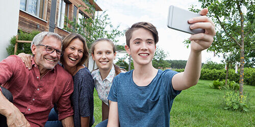 A teen boy takes a selfie of his family while they sit on the grass in their backyard.