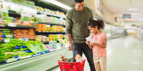 A father standing in the produce section of a grocery store holds a red shopping basket while his daughter holds a shopping list and carefully checks the contents of the basket.