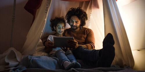A father and his daughter sit in a blanket fort and watch a movie on a tablet