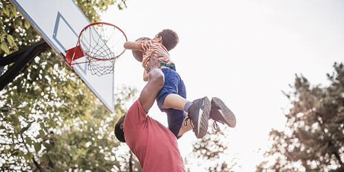 A dad in a red shirt lifts his son above his head to shoot a basketball into the hoop as they play outdoors