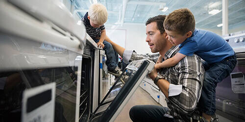 Father in appliance store kneels to look inside oven, with one son on his back and the other son sitting on top of the oven