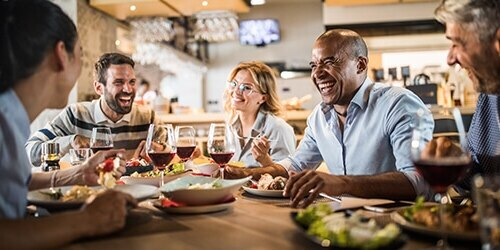 A group of friends enjoy laughter, glasses of red wine and a meal together in a casual restaurant