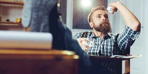Bearded Man with Feet Up on Desk Gets Ready to Throw a Piece of Paper