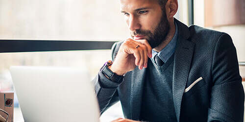 Bearded professional man resting his chin on his hand looks intently at his laptop while he types with his other hand