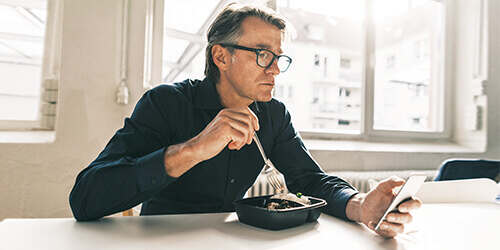 A man in a black button down shirt and glasses, sits at a table eating with a fork, while using his mobile phone.