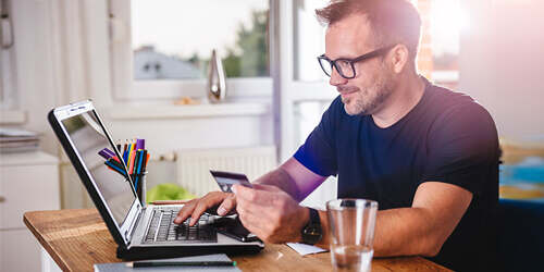A man in a black tshirt and glasses sits at his laptop with a glass of water in a bright white room and holds a credit or debit card as he types in the information