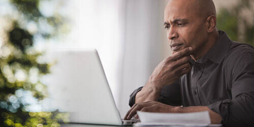 A man in a black shirt touches his face with his hand in thought as he looks at his laptop.