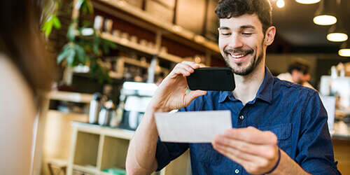 Bearded man smiles showing his friend how easy it is to make a mobile deposit to his bank from the comfort of a cafe