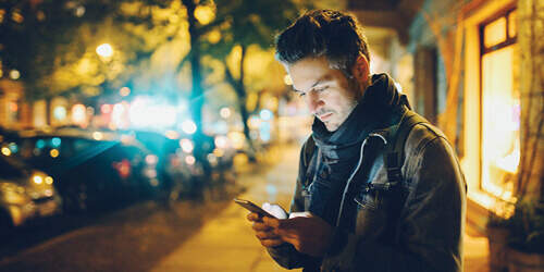 A man wearing a scarf and denim jacket stands on a car-lined sidewalk at night as he checks his phone for messages.