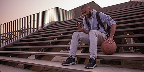 A smiling student with a backpack sits on outdoor bleachers holding his basketball as he checks his phone.