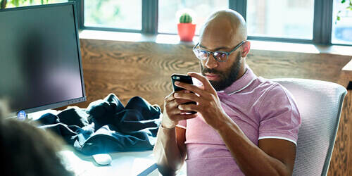 A bearded man with glasses and a pink shirt sits by his desktop computer and checks his phone, with a small cactus on the windowsill behind him.
