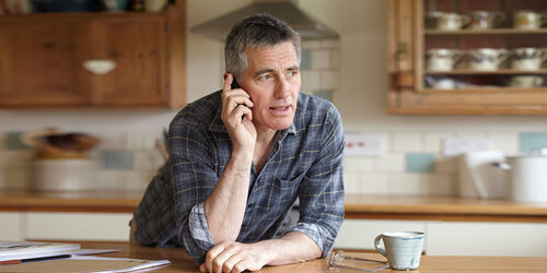 A gray-haired man in a plaid shirt leans on his kitchen counter as he talks on his mobile phone.