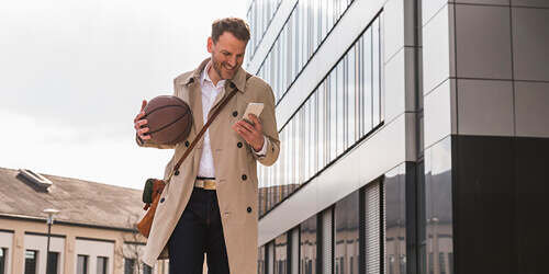 A business man in a tan coat and bag walks out of a building holding a basketball as he texts on his phone