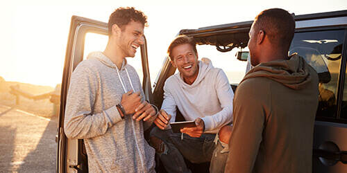 Three male friends stand at a car talking and laughing while one holds a mobile phone.