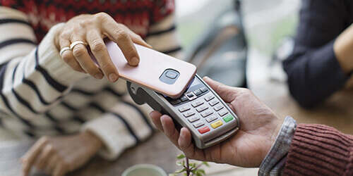 Closeup of a woman's hands holding her mobile phone against a card terminal for payment