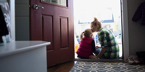 Mother kisses her your daughter on the top of her head while they sit in the doorway of their home on a cool sunny day