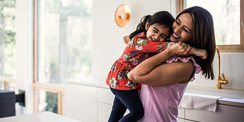 Mother in pink shirt lifts up and hugs her young daughter in white kitchen as they both share a laugh