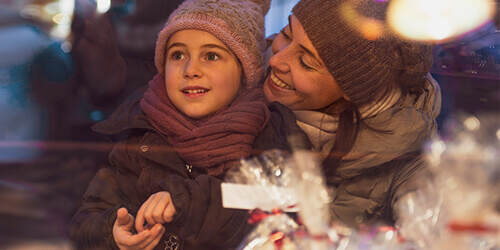 A mother smiles at her daughter as they peer into the window of a bakery shop both wearing winter coats and hats