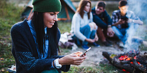 Young woman wearing a green knit hat looks at mobile phone and friends sit around the campfire talking in the background