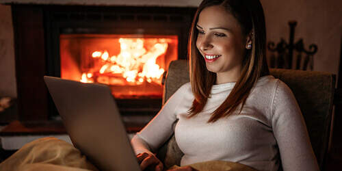 A woman in a white sweater sits under a blanket by a fire at home while using her laptop