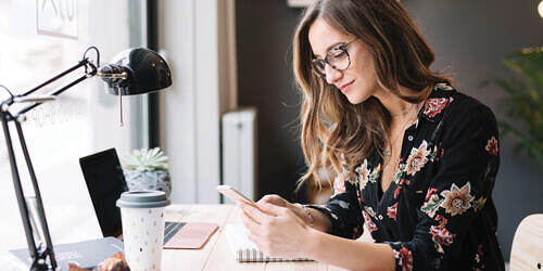 A woman with long hair, glasses and a floral shirt sits by a window at a desk with a lamp, coffee and laptop, as she checks her mobile phone