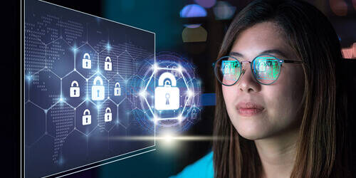 A woman in blue looks at a lock icon hologram display while the image reflects in her glasses.