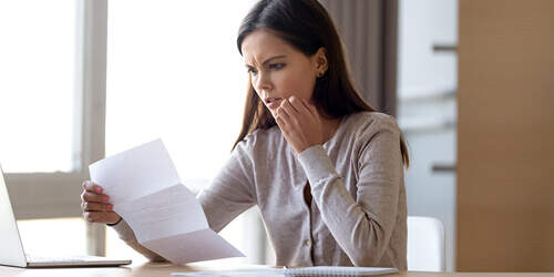 A woman with long dark hair reads a letter with a look of concern on her face.