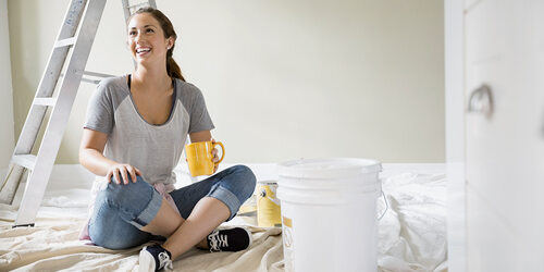 A woman in a gray tshirt and jeans sits cross-legged on the floor smiling holding a yellow coffee mug, with a ladder and paint can behind her