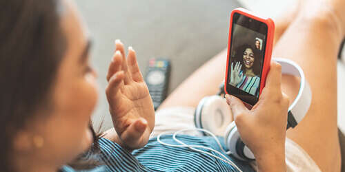 Looking over the shoulder of a woman, who is holding a red mobile phone waving hello to her friend on a video call.