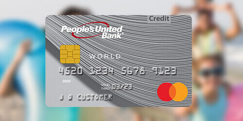 People's United Bank silver Mastercard Credit Card on a blurred background of a family on the beach